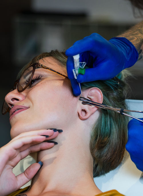 Portrait of a woman getting her ear pierced. Man showing a process of piercing ear with steril neadle and latex gloves. Ear Piercing Procedure
